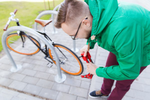 hipster man fastening fixed gear bike with lock